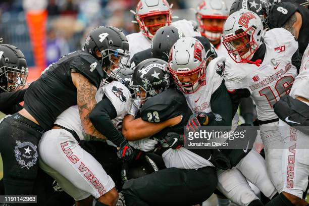 Running back Kelton Moore of the Nevada Wolf Pack is taken down by the UNLV Rebels defense during the first quarter at Mackay Stadium on November 30...