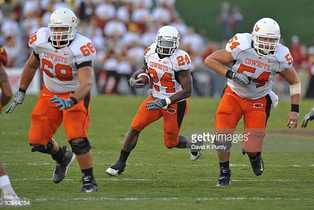 Running back Kendall Hunter of the Oklahoma State Cowboys rushes for yards up the middle with blocking help from teammates offensive lineman Lane...