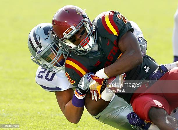 Running back Kene Nwangwu of the Iowa State Cyclones is tackled by defensive back Denzel Goolsby of the Kansas State Wildcats as he rushed for yards...