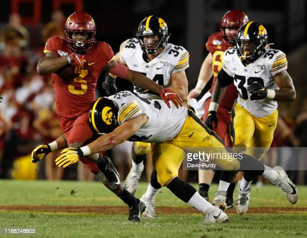 Running back Kene Nwangwu of the Iowa State Cyclones is tackled bye defensive end A.J. Epenesa of the Iowa Hawkeyes as he rushed for yards in the...