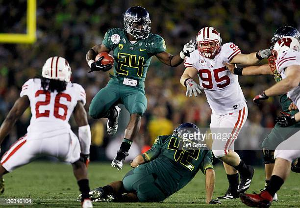 Running back Kenjon Barner of the Oregon Ducks leaps over teammate David Paulson in the second half against the Wisconsin Badgers at the 98th Rose...