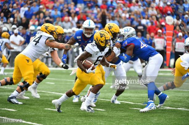 Running back Kennedy McKoy of the West Virginia Mountaineers rushes against the Kansas Jayhawks at Memorial Stadium on September 21 2019 in Lawrence...