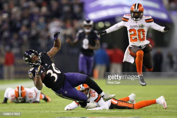 Running Back Kenneth Dixon of the Baltimore Ravens is tackled by strong safety Damarious Randall of the Cleveland Browns in the second quarter at M&T...