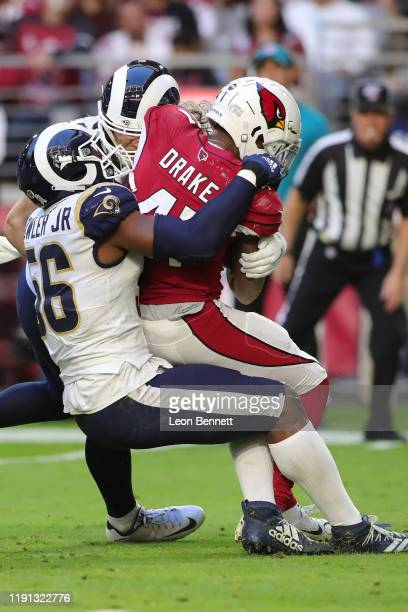 Running back Kenyan Drake of the Arizona Cardinals is stopped in the back field by defensive end Dante Fowler of the Los Angeles Rams at State Farm...