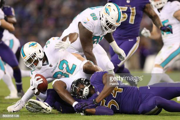 Running Back Kenyan Drake of the Miami Dolphins is tackled by linebacker Tyus Bowser of the Baltimore Ravens in the second quarter at MT Bank Stadium...