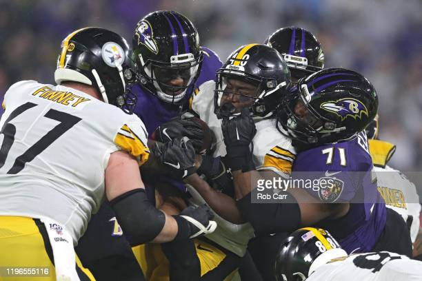 Running back Kerrith Whyte of the Pittsburgh Steelers is tackled by multiple Baltimore Ravens defenders during the second quarter at MT Bank Stadium...