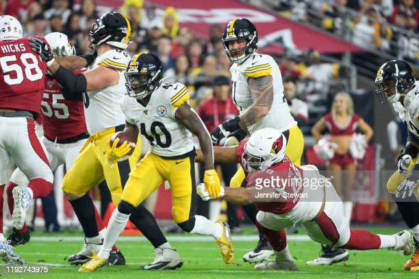 Running back Kerrith Whyte of the Pittsburgh Steelers runs with the ball in the first half against defensive tackle Corey Peters of the Arizona...