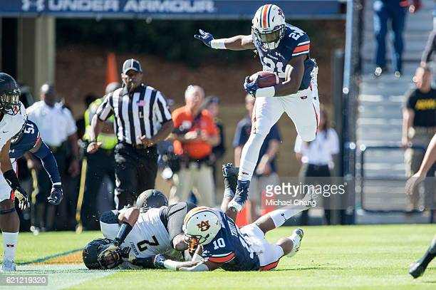 Running back Kerryon Johnson of the Auburn Tigers leaps over wide receiver Stanton Truitt of the Auburn Tigers and safety Arnold Tarpley of the...