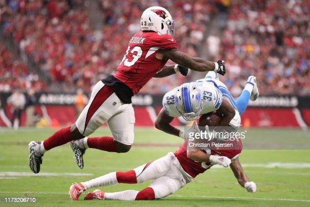 Running back Kerryon Johnson of the Detroit Lions is tackled by Byron Murphy and Haason Reddick of the Arizona Cardinals d1uring the first half of...