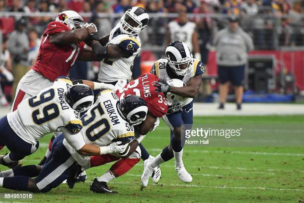 Running back Kerwynn Williams of the Arizona Cardinals is tackled by defensive end Aaron Donald linebacker Samson Ebukam and free safety Lamarcus...