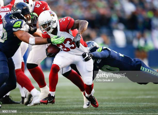 Running back Kerwynn Williams of the Arizona Cardinals is tackled by linebacker KJ Wright of the Seattle Seahawks and Bradley McDougald in the second...