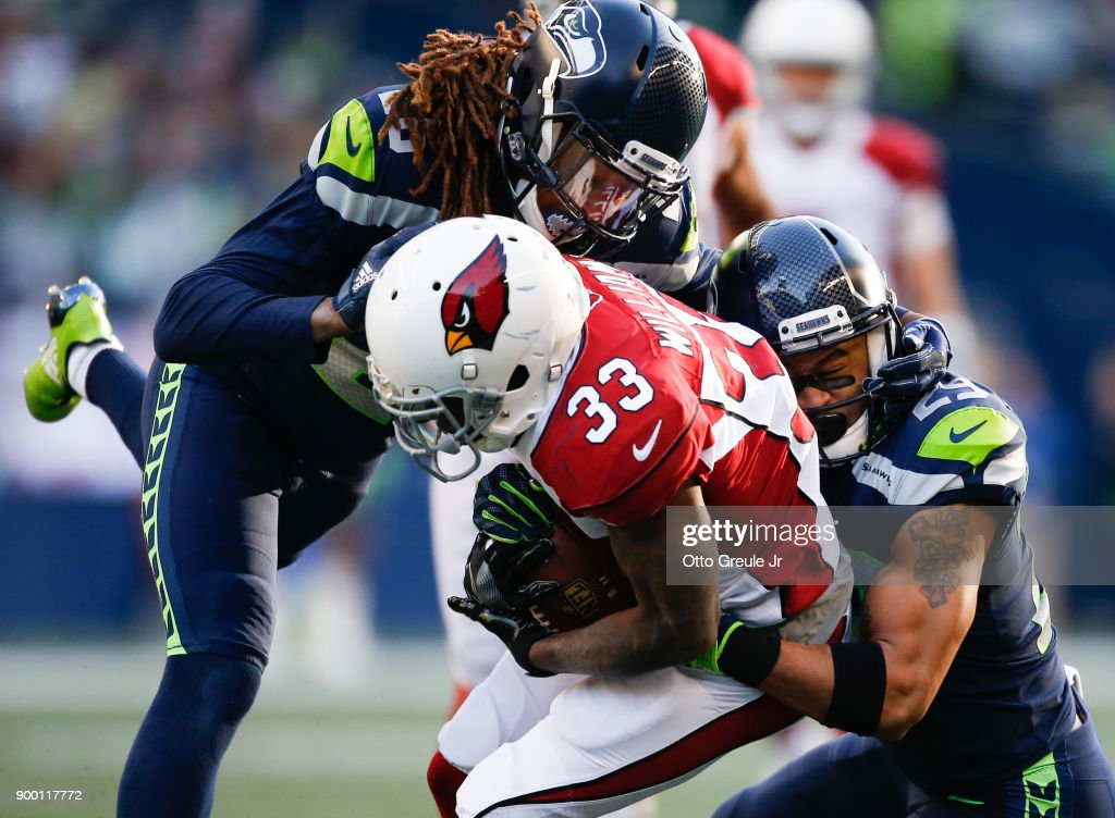 Running back Kerwynn Williams #33 of the Arizona Cardinals is tackled by cornerback Shaquill Griffin #26 of the Seattle Seahawks and Earl Thomas #29 in the first half at CenturyLink Field on December 31, 2017 in Seattle, Washington.