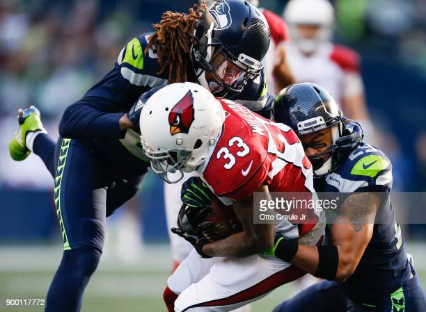 Running back Kerwynn Williams of the Arizona Cardinals is tackled by cornerback Shaquill Griffin of the Seattle Seahawks and Earl Thomas in the first...