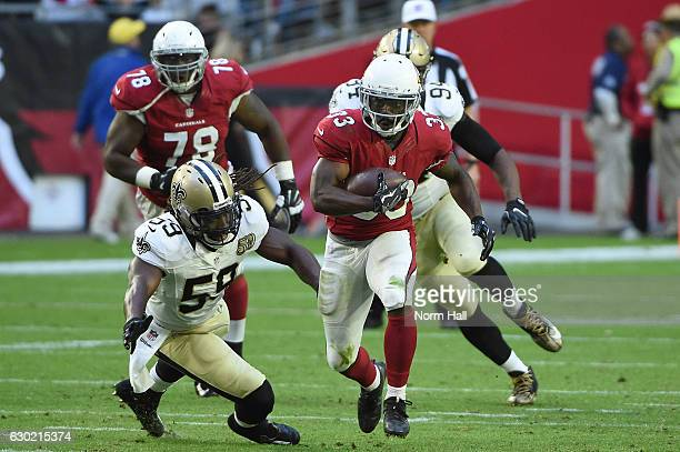 Running back Kerwynn Williams of the Arizona Cardinals runs with the football in front of outside linebacker Dannell Ellerbe of the New Orleans...