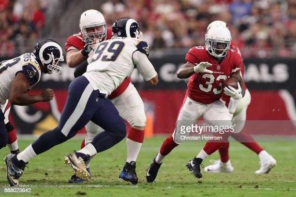 Running back Kerwynn Williams of the Arizona Cardinals rushes the football against defensive end Aaron Donald of the Los Angeles Rams during the NFL...