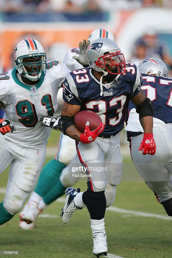 Running back Kevin Faulk #33 of the New England Patriots runs the ball while avoiding a tackle by Vonnie Holliday #91 of the Miami Dolphins at Dolphin Stadium on December 10, 2006 in Miami, Florida. The Dolphins defeated the Patriots 21-0.