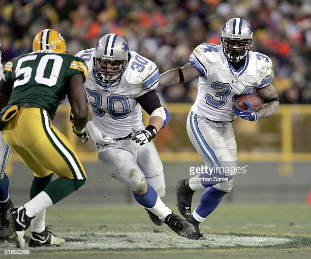 Running back Kevin Jones of the Detroit Lions finds running room behind the block of fullback Cory Schlesinger against linebacker Hannible Navies of...