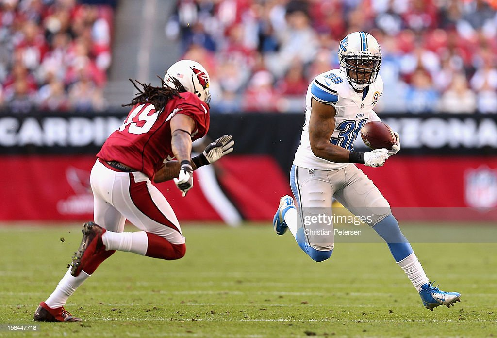 Running back Kevin Smith #30 of the Detroit Lions runs with the football against strong safety Rashad Johnson #49 of the Arizona Cardinals during the NFL game at the University of Phoenix Stadium on December 16, 2012 in Glendale, Arizona. The Cardinals defeated the Lions 38-10.