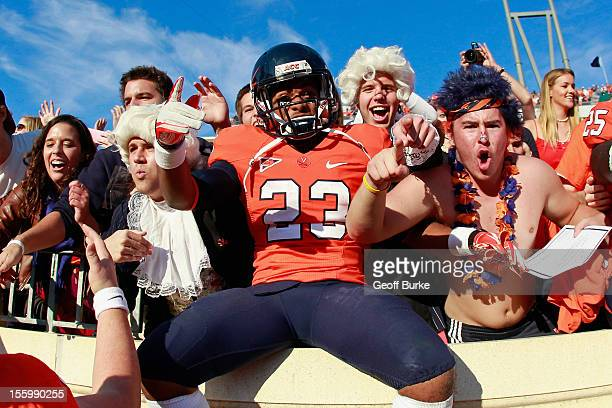 Running back Khalek Shepherd of the Virginia Cavaliers celebrates with fans in the stands after the Cavaliers game against the Miami Hurricanes at...