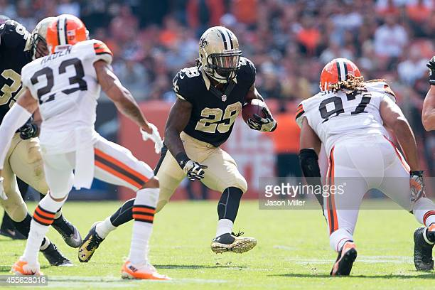 Running back Khiry Robinson of the New Orleans Saints caries the ball while under pressure from cornerback Joe Haden and outside linebacker Jabaal...