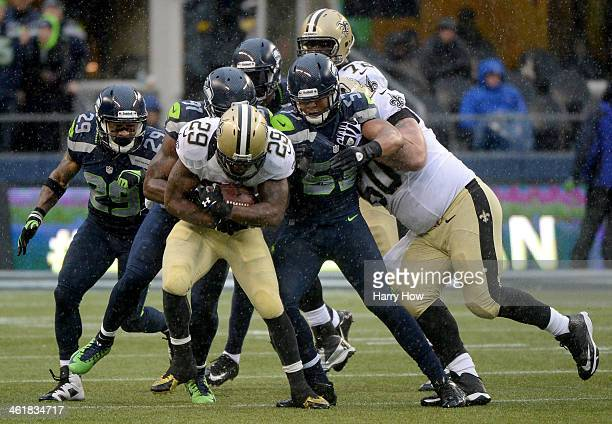 Running back Khiry Robinson of the New Orleans Saints is tackled in the second quarter by defensive end Chris Clemons of the Seattle Seahawks during...