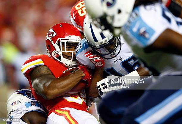 Running back Knile Davis of the Kansas City Chiefs is hit by wide receiver Tre McBride of the Tennessee Titans during the preseason game at Arrowhead...