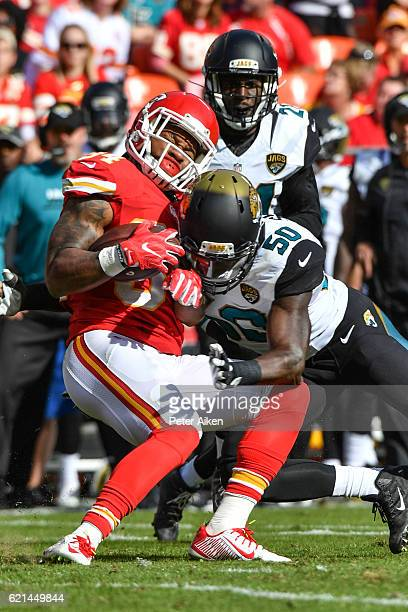 Running back Knile Davis of the Kansas City Chiefs is tackled by outside linebacker Telvin Smith of the Jacksonville Jaguars at Arrowhead Stadium...