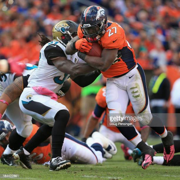 Running back Knowshon Moreno of the Denver Broncos breaks the tackle of strong safety John Cyprien of the Jacksonville Jaguars and rushes eight yards...
