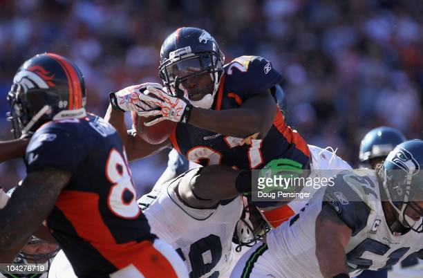 Running back Knowshon Moreno of the Denver Broncos goes over defensive tackle Colin Cole of the Seattle Seahawks for a one yard touchdown in the...