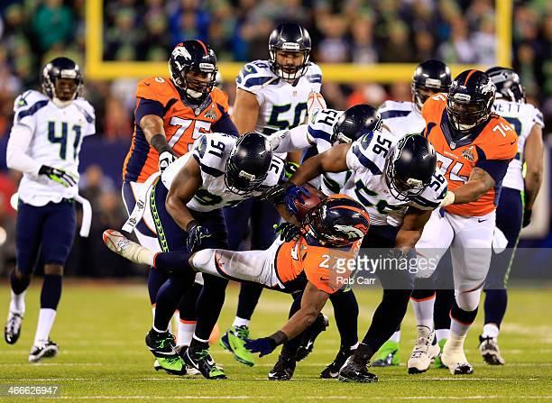 Running back Knowshon Moreno of the Denver Broncos is tackled by defensive end Chris Clemons defensive end Cliff Avril and middle linebacker Bobby...