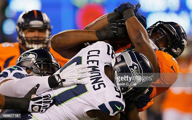 Running back Knowshon Moreno of the Denver Broncos is tackled by defensive end Chris Clemons and defensive end Cliff Avril of the Seattle Seahawks in...