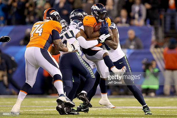 Running back Knowshon Moreno of the Denver Broncos is tackled by defensive end Chris Clemons defensive end Cliff Avril and outside linebacker KJ...