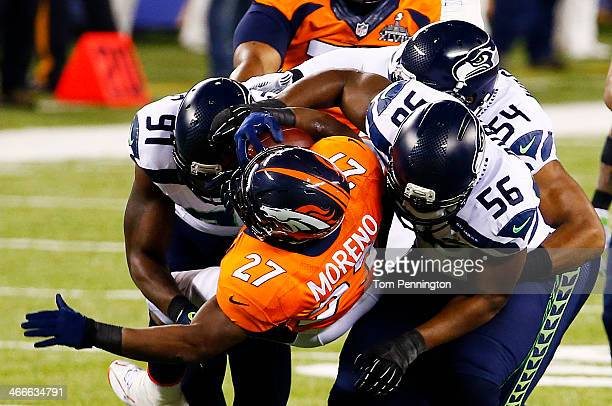 Running back Knowshon Moreno of the Denver Broncos is tackled by defensive end Cliff Avril middle linebacker Bobby Wagner and defensive end Chris...