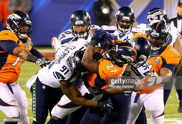 Running back Knowshon Moreno of the Denver Broncos is tackled by Chris Clemons defensive end Cliff Avril and outside linebacker KJ Wright of the...