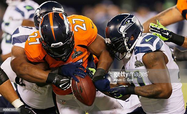 Running back Knowshon Moreno of the Denver Broncos is tackled by defensive tackle Clinton McDonald and defensive end Chris Clemons of the Seattle...