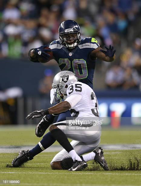 Running back Kregg Lumpkin of the Seattle Seahawks rushes against Chimdi Chekwa of the Oakland Raiders at CenturyLink Field on August 30 2012 in...