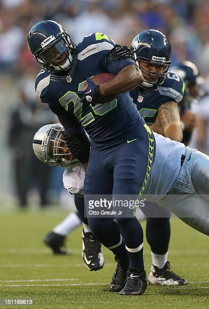 Running back Kregg Lumpkin of the Seattle Seahawks rushes against Jack Crawford of the Oakland Raiders at CenturyLink Field on August 30 2012 in...