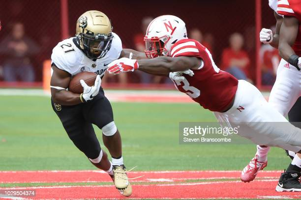 Running back Kyle Evans of the Colorado Buffaloes avoids the tackle of linebacker Tyrin Ferguson of the Nebraska Cornhuskers at Memorial Stadium on...
