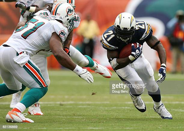 Running back LaDainian Tomlinson of the San Diego Chargers runs into the defense of linebackers Channing Crowder and Akin Ayodele the Miami Dolphins...