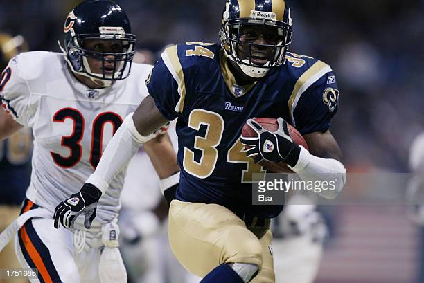 Running back Lamar Gordon of the St Louis Rams carries the ball and is chased by safety Mike Brown of the Chicago Bears during the game at the Edward...