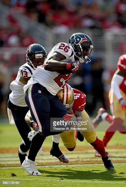 Running back Lamar Miller of the Houston Texans carries the ball and gets hit by strong safety Antoine Bethea of the San Francisco 49ers during the...