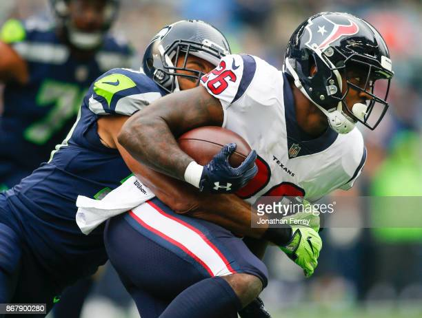Running back Lamar Miller of the Houston Texans is tackled by linebacker K.J. Wright of the Seattle Seahawks during the first quarter of the game at...