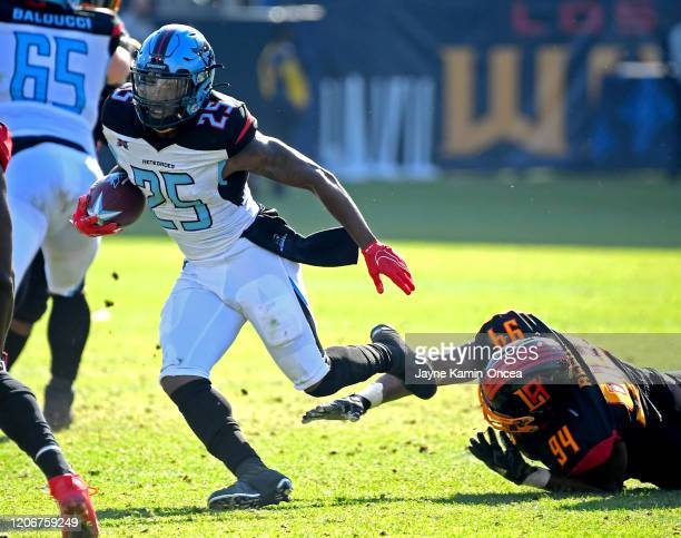 Running back Lance Dunbar of the Dallas Renegades breaks a tackle from defensive end Cedric Reed of the Los Angeles Wildcats in the game at Dignity...