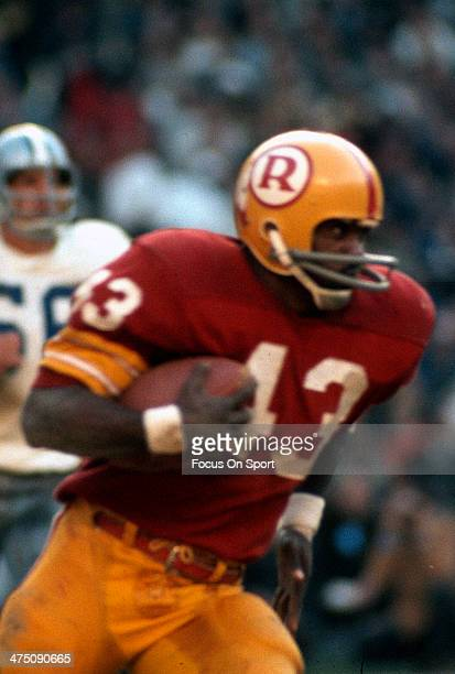 Running back Larry Brown of the Washington Redskins carries the ball against the Dallas Cowboys during an NFL football game circa 1970 at RFK Stadium...