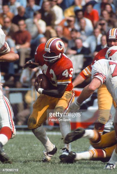 Running back Larry Brown of the Washington Redskins carries the ball against the St Louis Cardinals during an NFL football game circa 1972 at RFK...