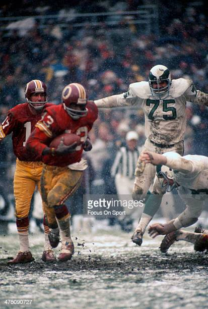 Running back Larry Brown of the Washington Redskins carries the ball against the Philadelphia Eagles during an NFL football game circa 1972 at RFK...