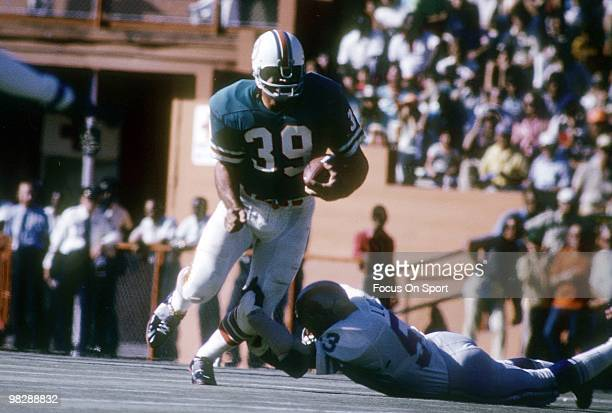 Running back Larry Csonka of the Miami Dolphins with the ball tries to get free from the grasp of linebacker Mike Lucci of the Detroit Lions December...