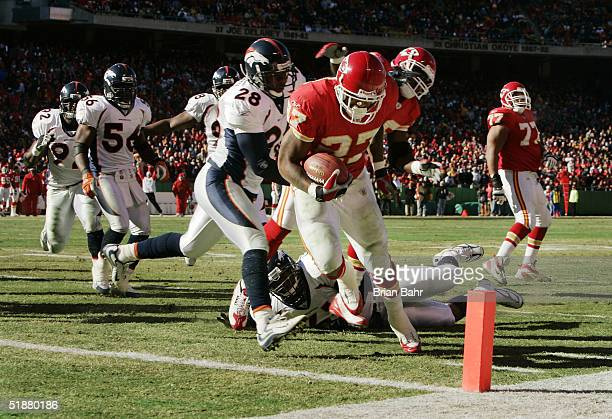 Running back Larry Johnson of the Kansas City Chiefs slips into the endzone in front of safety Kennoy Kennedy and defensive tackle Ellis Johnson of...