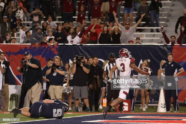 Running back Larry Rose III of the New Mexico State Aggies scores the game winning touchdown past linebacker David Woodward of the Utah State Aggies...
