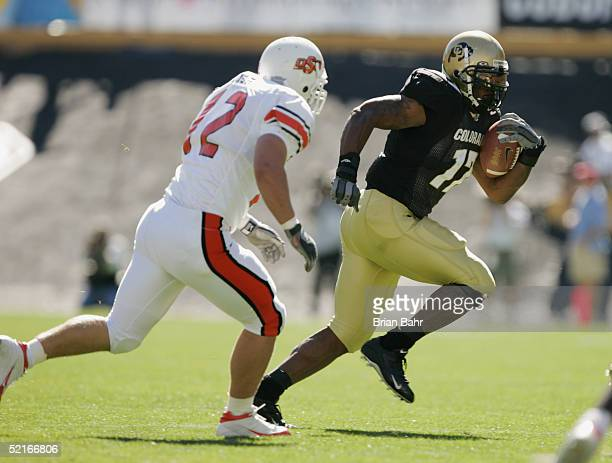 Running back Lawrence Vickers of the Colorado Buffaloes runs against linebacker Paul Duren of the Oklahoma State Cowboys on October 9, 2004 at Folsom...